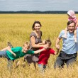Cute family at field - Stock Photo