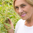 Aged woman at plants — Stock Photo #6786389
