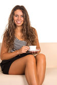 Girl with a cup on sofa — Stock Photo