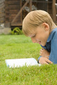 Boy with book on grass — Stock Photo