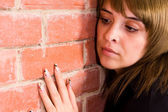 Cute girl at wall — Stock Photo