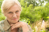 Old woman in forest — Stockfoto