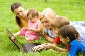 Family with laptop at nature — Stock Photo