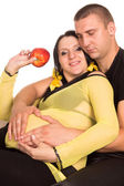 Pregnant woman on sofa with man — Foto de Stock