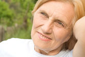 Old happy woman at nature — Stock Photo