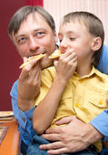 Man and son with pizza — Stock Photo