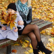 Little girl and mom with leaves — Stock Photo #7381462