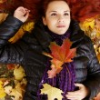 Cute girl lying on leaves — Stock Photo