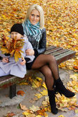 Little girl and mom with leaves — Stock Photo
