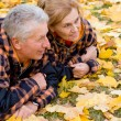 Old couple lying on leaves — Stockfoto