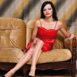 Woman in red at sofa — Foto de Stock