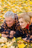 Old couple lying on leaves — Stock Photo