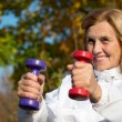 Elderly woman with dumb bells — Stock Photo