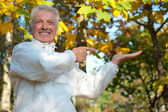 Old guy at autumn park — Stock Photo