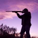 日没で散弾銃を持つハンター — ストック写真