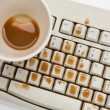 Coffee and damaged computer keyboard — Stock Photo