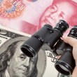 Binoculars and dollar, chinese yuan — Stock Photo