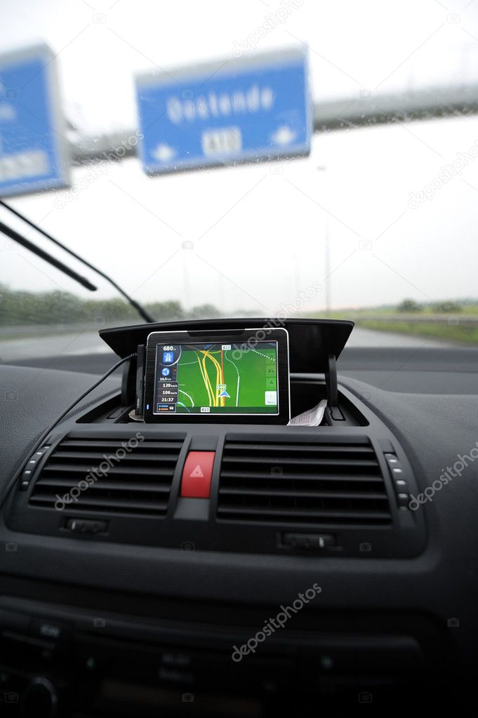 Portable GPS Unit on automobile dashboard showing direction on a rainy day.  Stock Photo #6819046