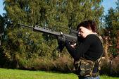 Beautiful girl with a gun — Stock Photo