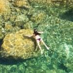Woman swimming on the rocks — Stock Photo