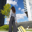 Businesswoman with suitcase and business building — Stock Photo