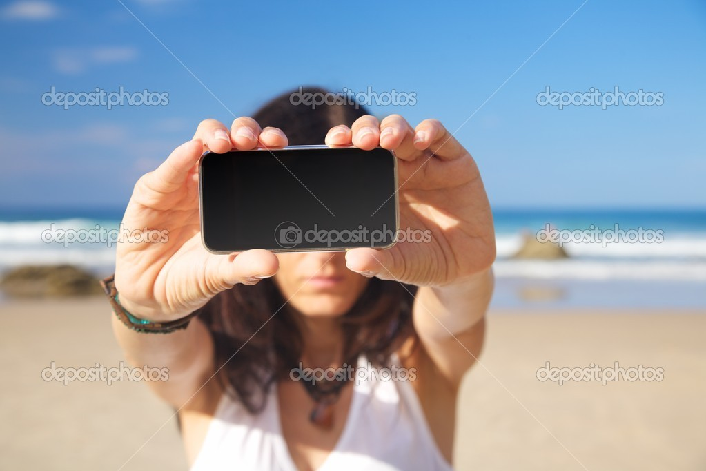 Smart phone in woman hand on a beach in Asturias Spain — Zdjęcie stockowe #6857703