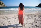 Red woman walking towards sea — Stock Photo
