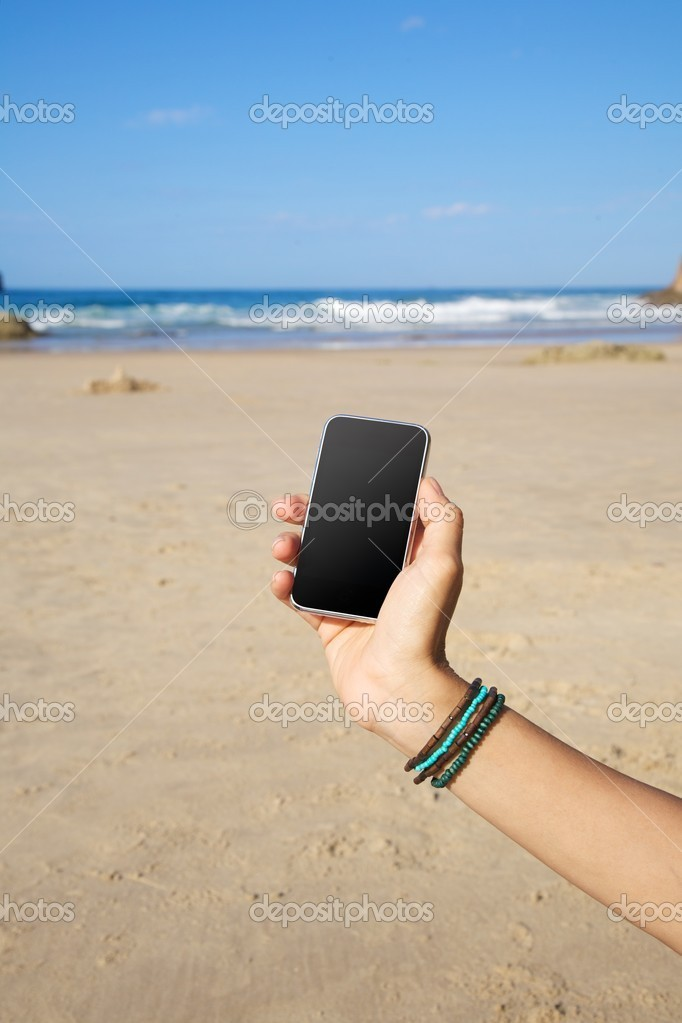 Smart phone in woman hand on a beach in Asturias Spain — Stock Photo #6941035