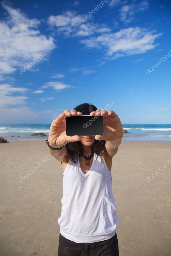 Smart phone in woman hand on a beach in Asturias Spain — Stock Photo #6941069
