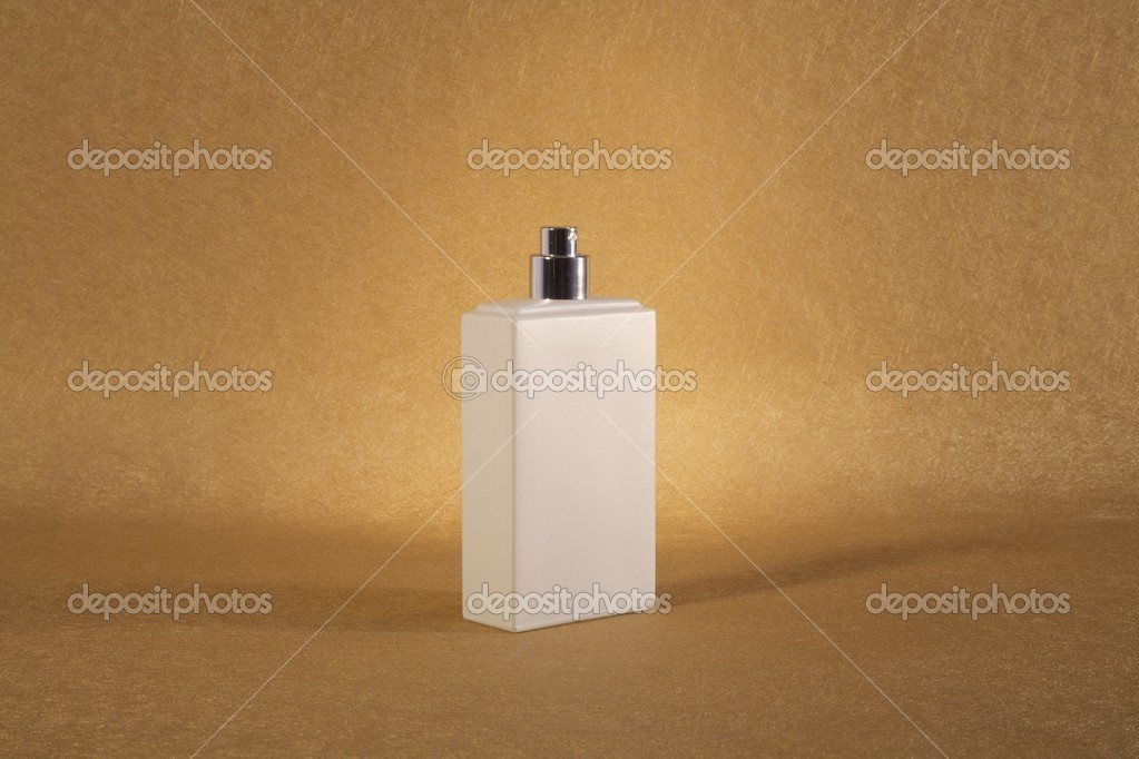 White spray bottle on golden textured paper at still life  Stock Photo #6955250
