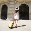 Woman back walking with suitcase — Stock Photo