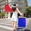 Happy woman walking with shopping bags on crosswalk — Stock Photo #7278628