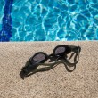 Stock Photo: Goggles on curb of swimming pool