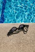 Goggles on curb of swimming pool — Stock Photo