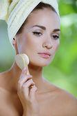 Belle jeune femme nettoie le visage avec une brosse souple — Photo