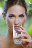 Beautiful young girl drinks water from glass outdoor — Stock Photo