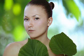 Young healthy woman with green leaf in her hands — Stock Photo