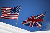 Amerikanska och brittiska flaggor i den blå himlen — Stockfoto