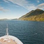Cruise ship sailing towards mountain — Stock Photo
