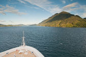 Cruise ship sailing towards mountain — Stock Photo