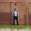 Young handsome man standing near the wall — Stock Photo