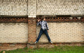 Young handsome man standing near old brick wall — Stock Photo