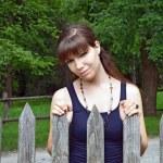 Girl near vintage rural fence — Stock Photo
