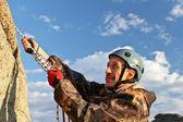 The rock-climber in helmet moves on top — Fotografia Stock