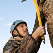 Stock Photo: The climber hammers in hook into rock