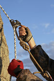 Hands of climber I work with equipment on rock. — Stock Photo