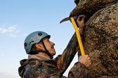 The climber hammers in hook into rock — Stock Photo