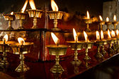 Some rows of candles in Tibetan temple — Stock Photo
