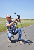 Young man with tripod — Stock fotografie