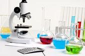 Flasks, microscope, calculator, workplace — Stock Photo